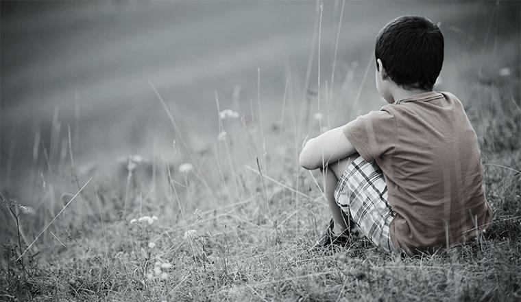 niño de espaldas sentado pensando en ser feliz después de haber vivido una infancia traumática