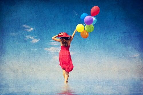 Mujer andando sobre el mar con globos de colores