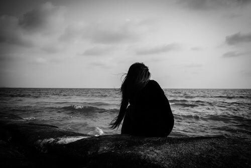 Mujer joven sola sentada encima de las rocas observando el mar
