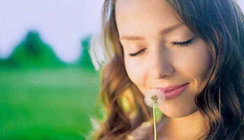 Mujer feliz pensando en el pasado mientras huele un diente de león