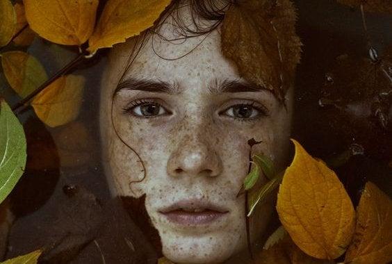 Chico triste rodeado de hojas