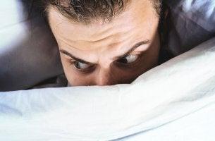 Hombre asustado cama por terrores nocturnos