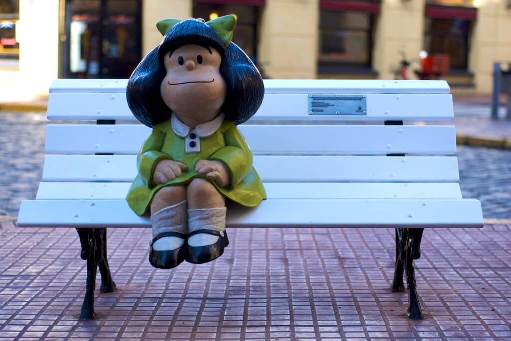 Mafalda sentada en un banco