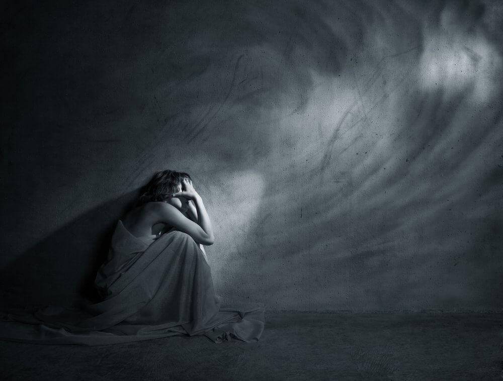 Mujer triste al lado de la pared