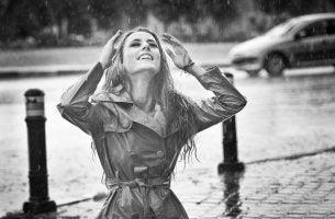 Mujer bajo la lluvia qeu sonríe con felicidad