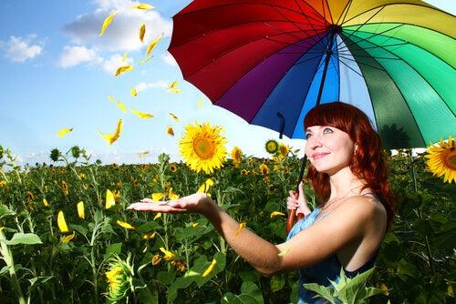 Mujer con un paraguas de colores demostrando felicidad