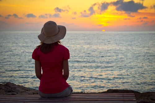 Mujer con miedo a morir pensando frente al mar