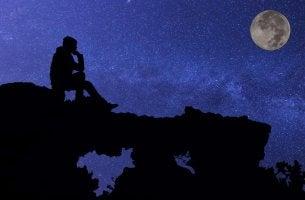 Hombre sentado en una piedra observando a la luna