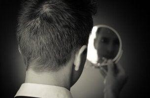 Hombre mirándose a un espejo para representar la personalidad egocéntrica