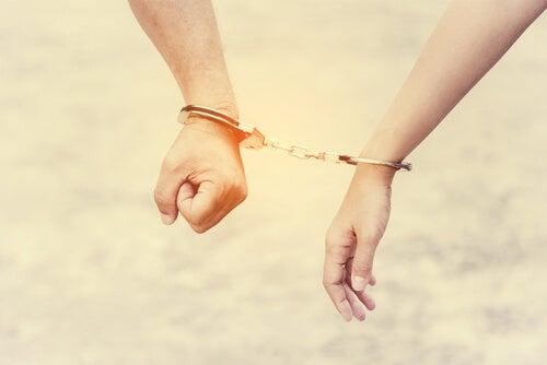 Manos encadenadas que simbolizan necesidad de aprobación