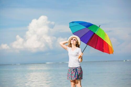 Mujer que sonríe con optimismo y un paraguas de colores