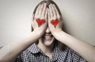 Mujer tapándose los ojos con corazones simbolizando amor ciego