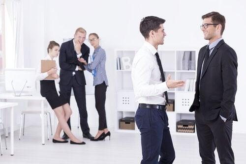 Personas envidiosas cuchicheando en el trabajo