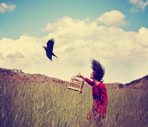 Mujer liberando un pájaro de la jaula