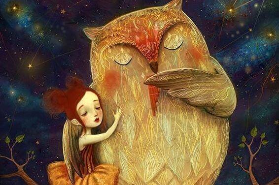 Niña con los ojos cerrados abrazada a un búho