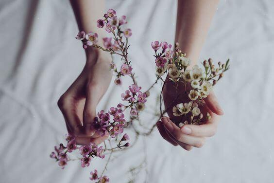 Manos con flores para dar las gracias