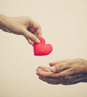 Mano dando un corazón a otra como gesto de ayuda