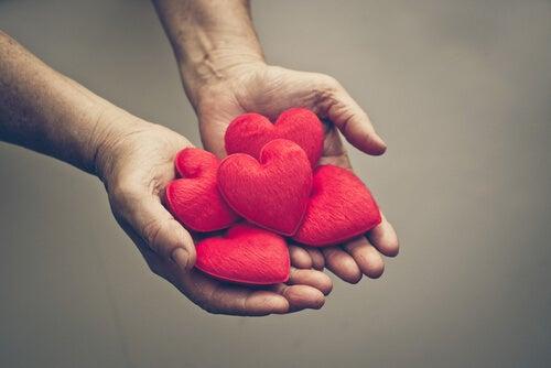 Mano ofreciendo corazones