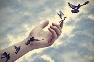 Manos soltando pájaros simbolizando reactancia psicológica