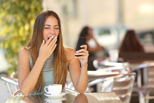 Mujer con un móvil bostezando y pensando me aburro