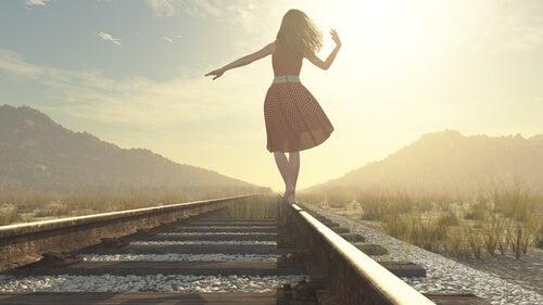 Mujer en una vía de tren buscando sus oportunidades