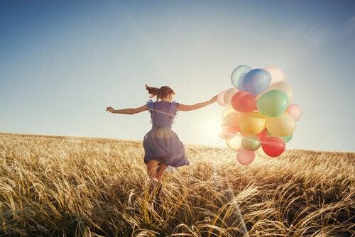 Mujer con globos feliz y demsotrando inteligencia emocional