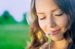 Mujer pensando mientras huele un diente de león