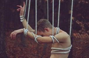 Hombr atado con cuerdas representando el rencor
