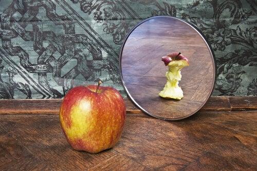 Manzana con complejos mirándose a un espejo