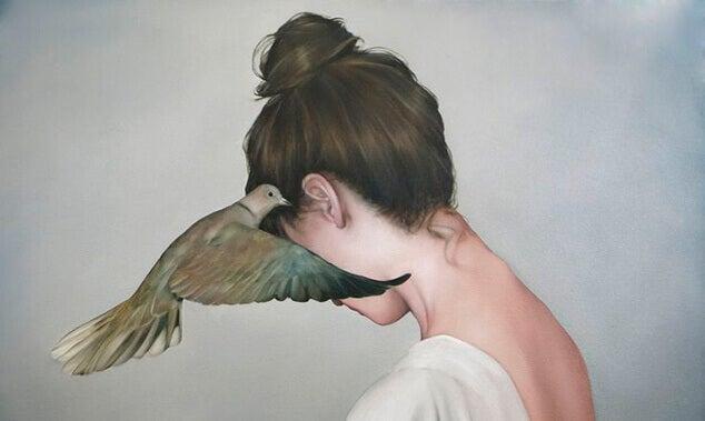 Mujer con una paloma en el oído dejándose llevar por el rencor