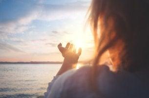 Mujer mirando al sol pensando en cómo conectar con la esperanza