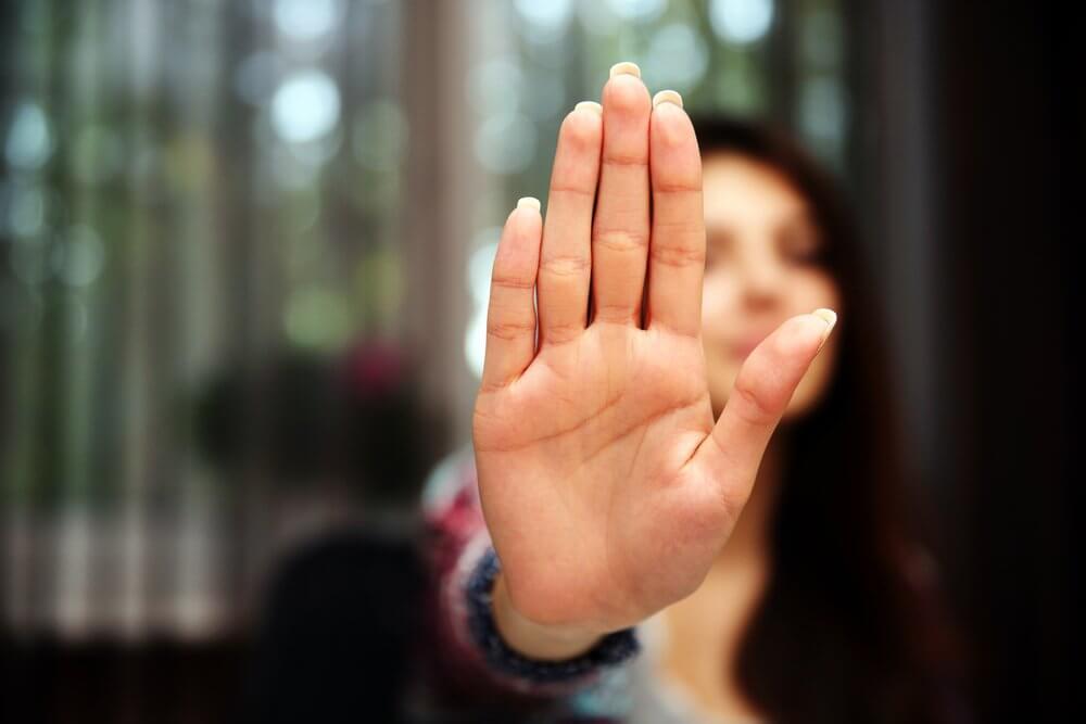 Mujer parando con la mano