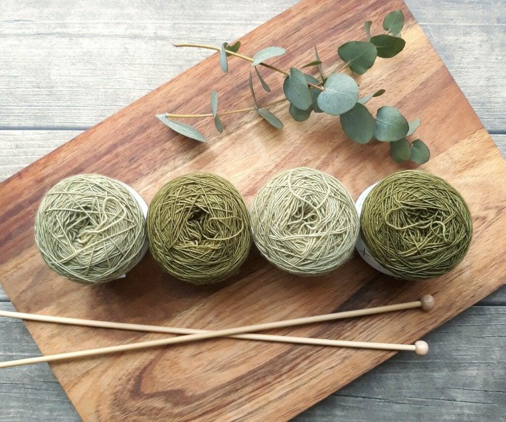 Bolas de lana verde y agujas de tejer