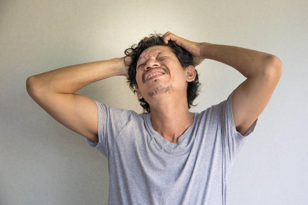 Hombre con un trastorno psicológico y las manos en la cabeza