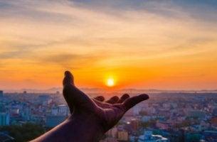 Mano cogiendo el sol como símbolo de ambición