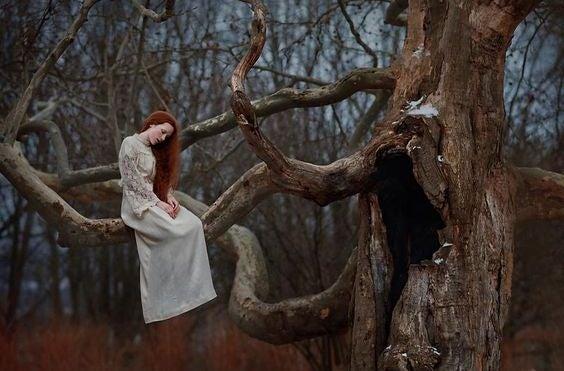Mujer triste en un árbol pensando en sus demonios
