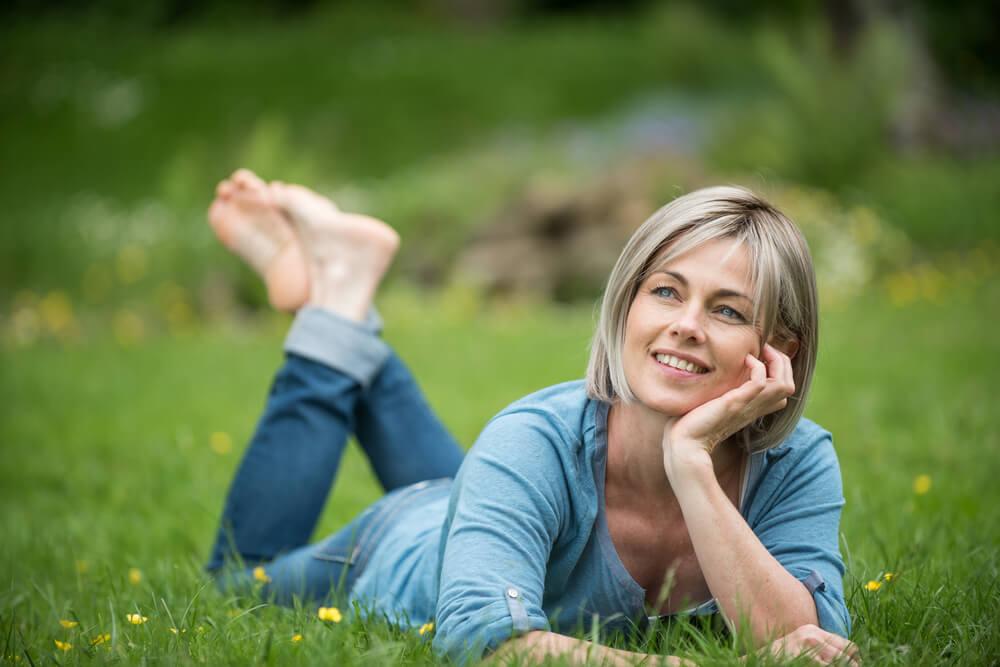 Mujer sobre la hierba feliz tras superar la crisis delos 40