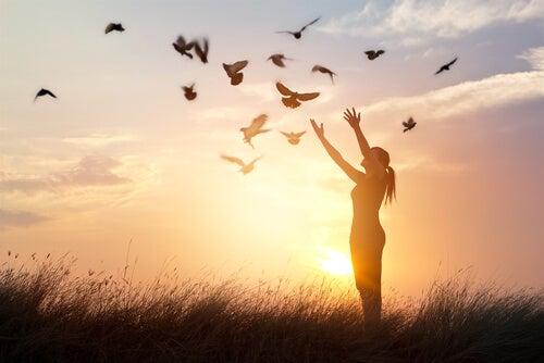 Mujer soltando pájaros que significan remordimientos