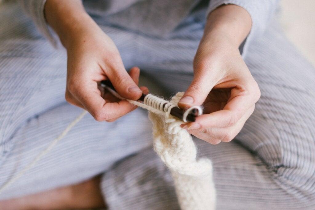 Mujer tejiendo en su cama