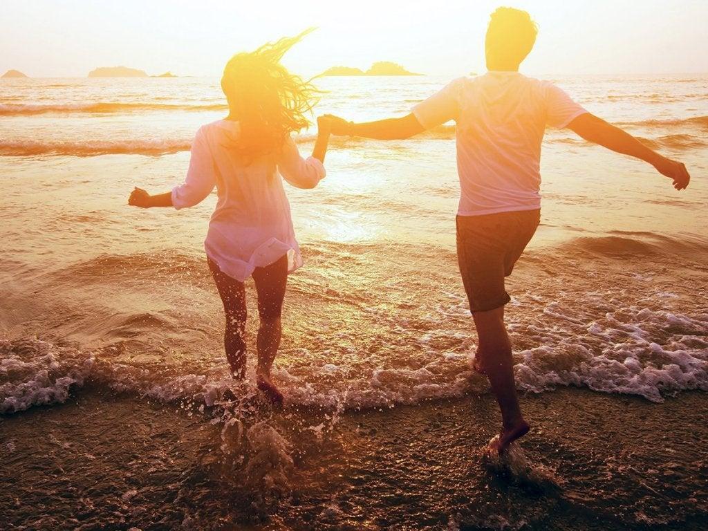 Pareja dándose la mano en la playa