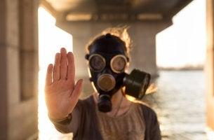 Persona con máscara de gas frenando relaciones tóxicas en la familia