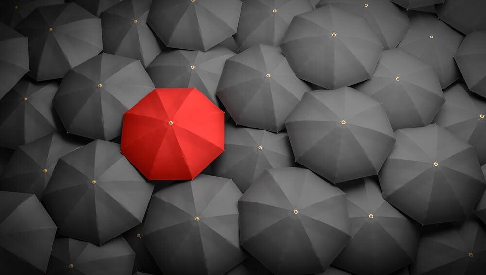 paraguas rojo entre paraguas negros