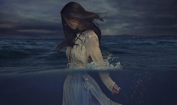 Mujer triste caminando por el mar