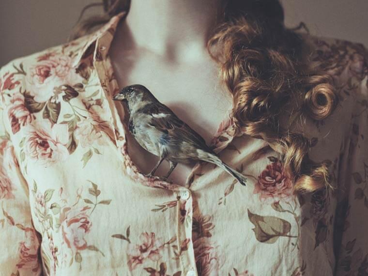 Mujer con pájaro en su pecho