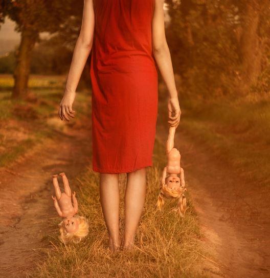 Mujer dejando caer muñecos