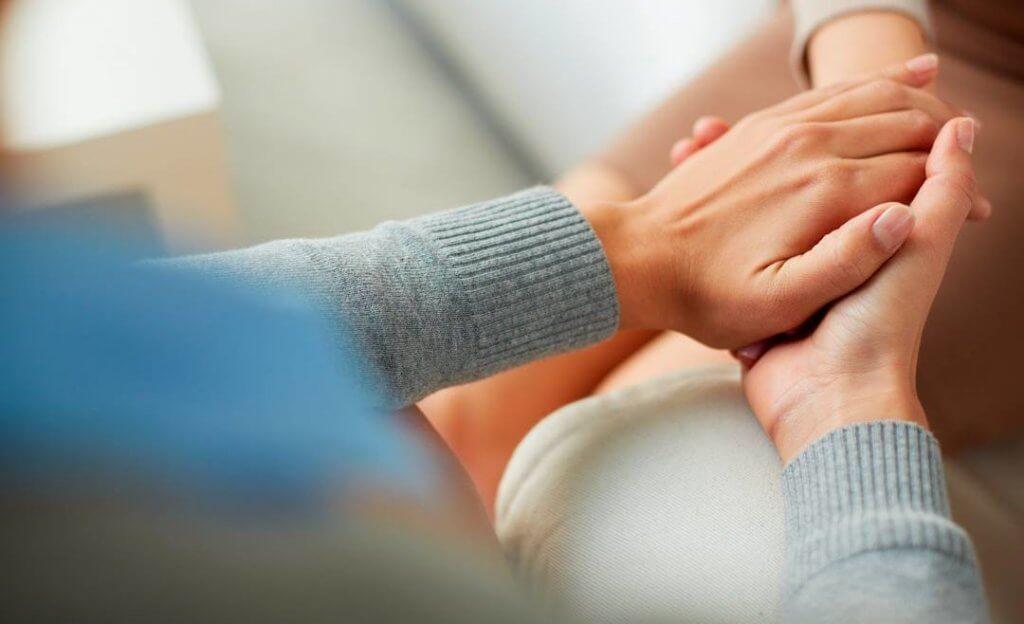 Persona cogiendo la mano a otra