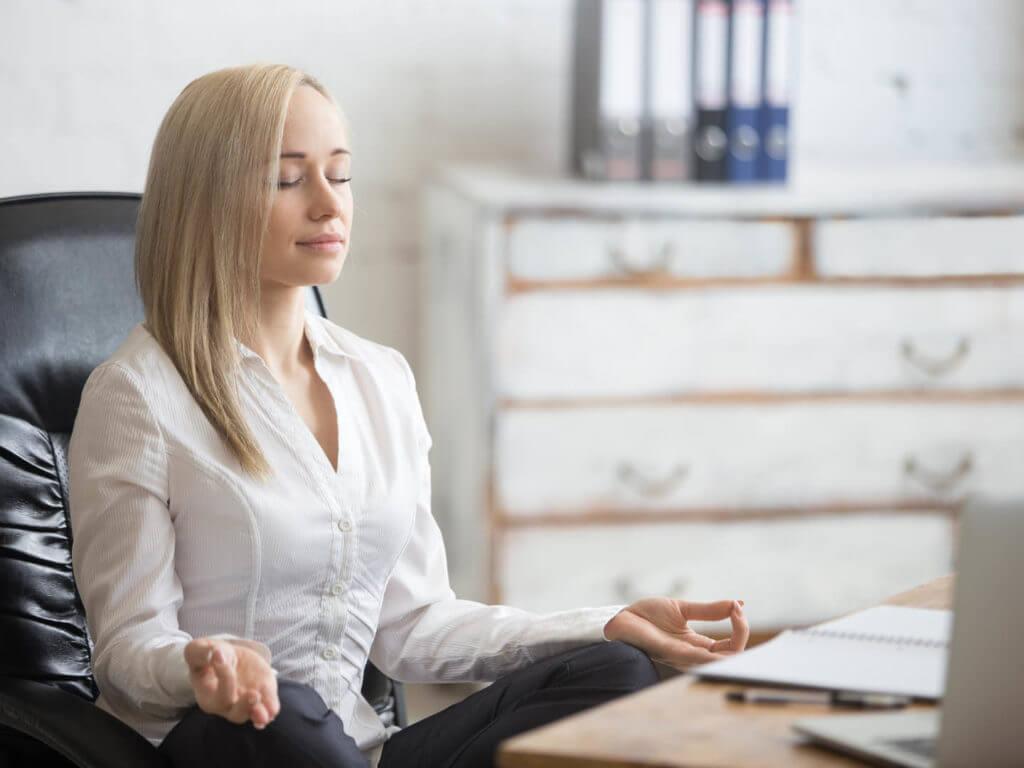 Mujer relajándose en el trabajo por el entrenamiento de inoculación de estrés