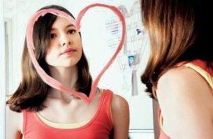 chica-mirandose-en-espejo-con-corazón