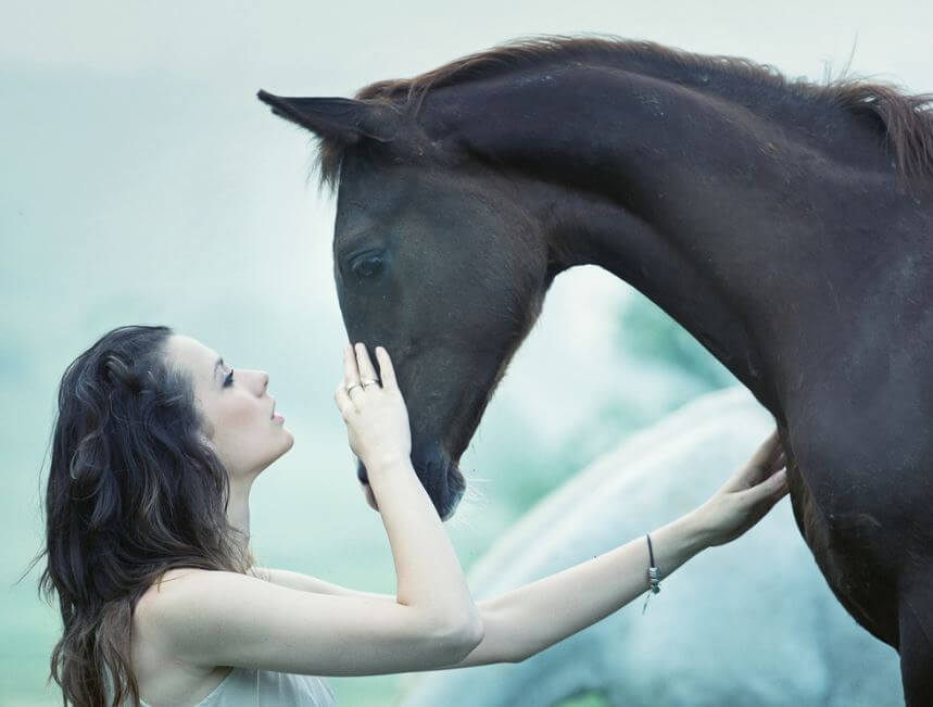 Mujer acariciando la cara de un caballo mientras lo mira a los ojos