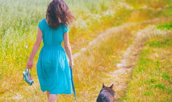Mujer caminando por el campo con su perro